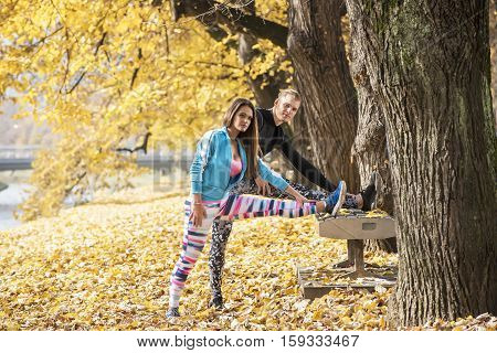 Beautiful Young Couple Stretching Together And Cool Down After Training In The Park. Autumn Environm