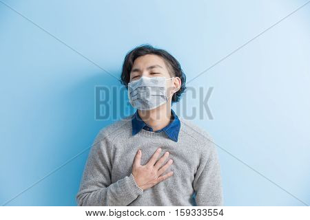 man feel heart pain isolated blue background asian