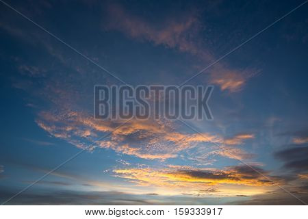 Beautiful sunset with dramatic orange clouds and dark blue sky.