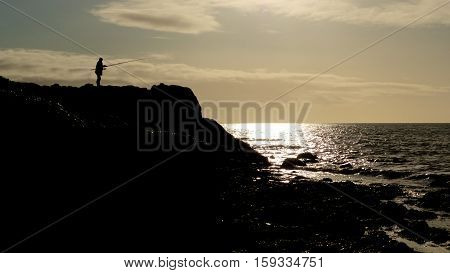 A lone Angler fishes from a rocky shelf at Arndale on the Lancashire coast UK. He is silhouetted against a dusky sky with the setting sun reflected on the ocean