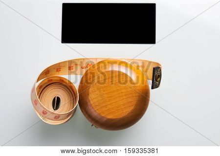 Yo-yo effect in diet concept. Wooden yoyo with centimeter measure. Weight bathroom scale with black display. Flat lay top view.