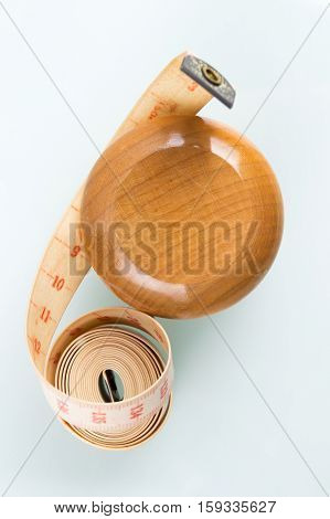 Yo-yo effect in diet concept. Wooden yoyo with centimeter measure. Reflective glass background. Flat lay top view. Vertical orientation.