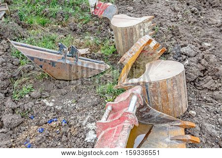 Excavator buckets are lie scattered around on the ground various types and many different sizes.