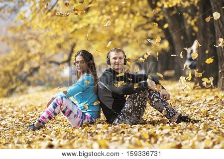 Beautiful Young Couple Resting And Listening Music After Successful Training In The Park. Autumn Env