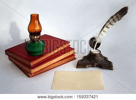 Blank paper card an oil lamp and a bronze inkwell with a quill pen as a concept of writing letters and greetings on holidays