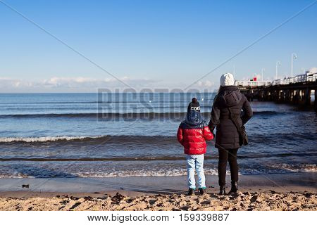 Little boy with his mother at the beach at winter