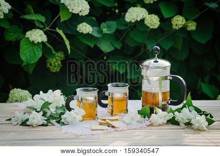 Cup of tea with jasmine, on table, on green background