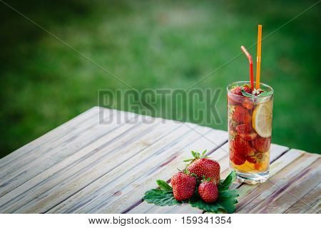 Glass of cold fresh summer bright strawberry lemonade on a table with creative composition, strawberries and fresh mint, soft focus