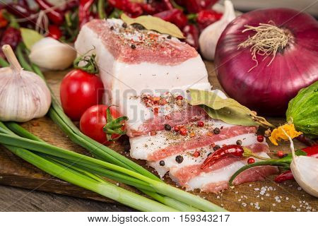 Slices of salted lard with spices and vegetables on wooden cutting board