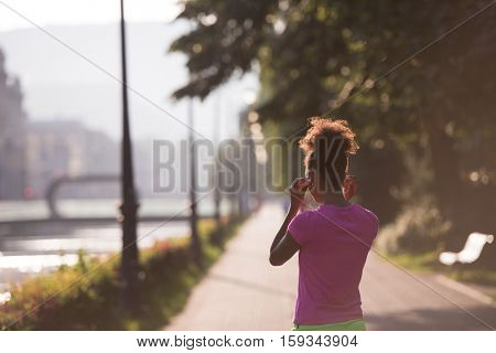 portrait of young african american jogging woman before running on early morning with sunrise in background
