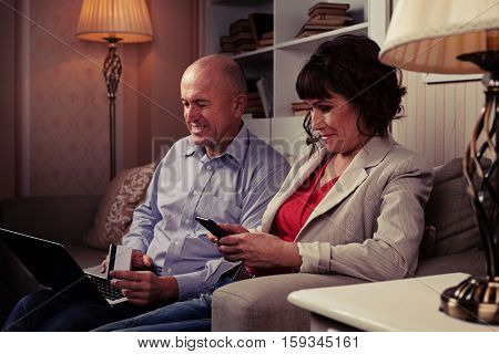 A mid side shot of smiling people sitting on the brown settee surrounded by lamps and booksettle. Man with laptop laughing and riant lady looking at her mobile