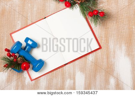 Christmas Sport Composition With Dumbbells, Notebook, Berries And Spruce