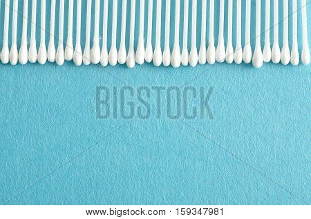 A row of cotton swabs isolated on a light blue background