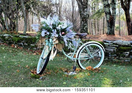 A mint green ladies bicycle parked in front of a moss covered  stonewall and dressed for the holidays.