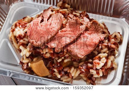 Healthy lunch. Creative food closeup. Weight loss diet, take away in foil box. Steamed veal pastrami with brown rice. Restaurant meal in container
