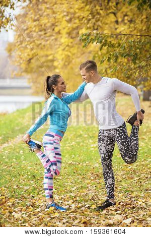Beautiful Young Couple Stretching Together And Preparing For Run In The Park. Autumn Environment.