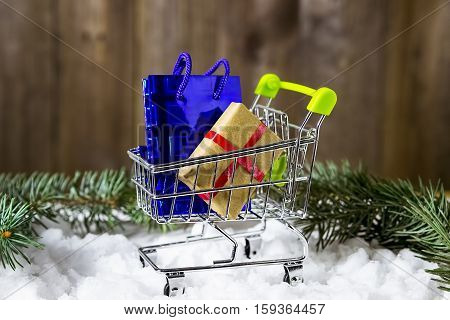 Christmas gifts in a mini shopping cart. Celebratory  presents  in a shopping trolley.
