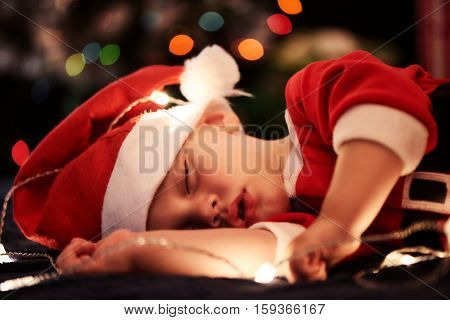 Baby boy peacfully sleeping while wearing a santa claus outfit, with beautiful bokeh from the christmas tree in the background, and fairly lights around the baby.
