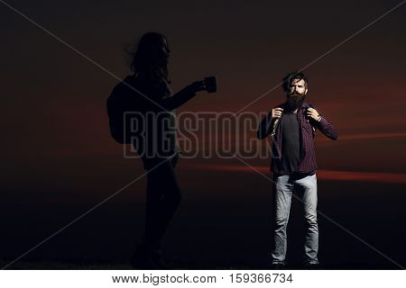 Dark silhouette of pretty girl with cup and bearded man hipster with beard and moustache on mountain top on night sky