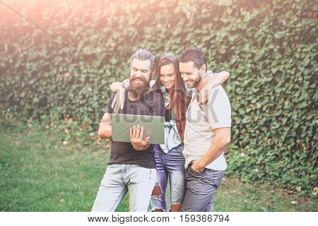 Cheerful Friends Use Laptop Computer