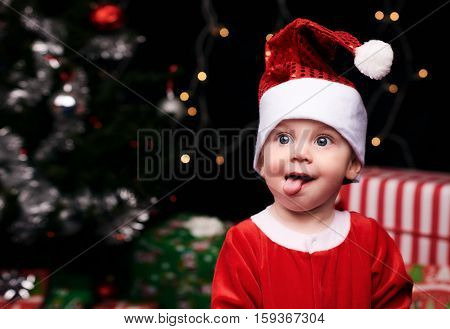 Baby sitting in front of a xmas tree pulling a silly face with his tongue out in a santa claus outfit with christmas gifts.