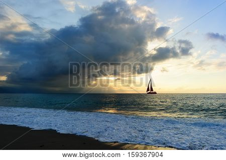 Ocean sunset sailboat sun ray silhouette is a bright uplifting seascape with sun beams breaking through the clouds as a sailboat is sailing along the ocean water..