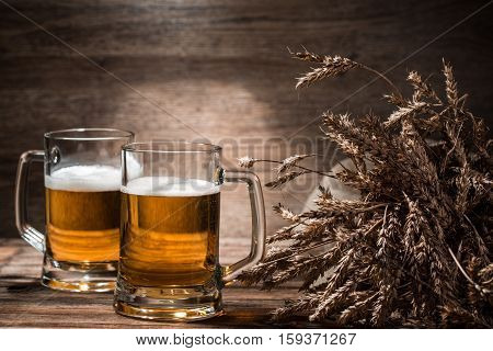 Two mugs of beer froth with wheat spikelets on empty wooden background