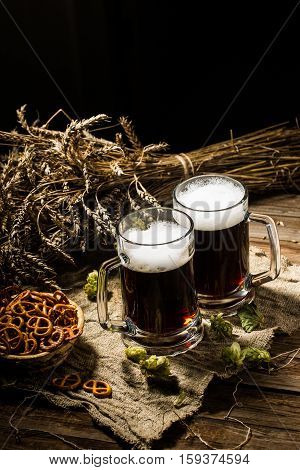 Two tankard beer with wheat and hops , basket of pretzels on wooden table
