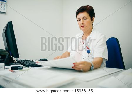 Digitizing medical records for better treatment. Experienced doctor working on her computer. Medical and healthcare concept.Older retiring doctor learning how to use computer at work