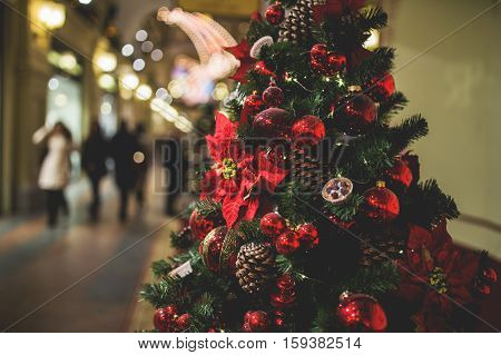 Christmas pine tree in lobby of store on background of people walking, photo toned