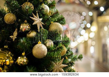 Festive pine with golden decorations on blurred background shopping center
