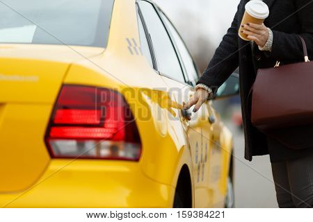 Girl with coffee in hand opens door of yellow taxi
