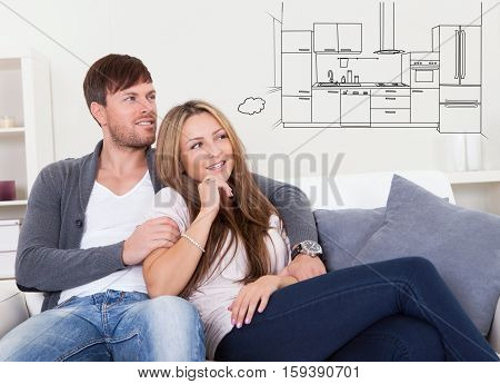 Young Couple Relaxing On Couch Thinking Of Having Modern Kitchen In Their House