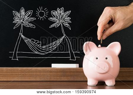 Close-up Of Person Hand Saving Money In Piggybank For Enjoying Vacation On Beach