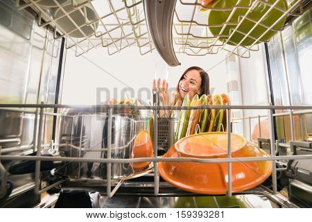 Young Happy Woman Looking At Clean Glass In Dishwasher
