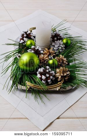 Christmas centerpiece with snowy pine cones on the serving tray. Christmas background with candle and green ornaments .