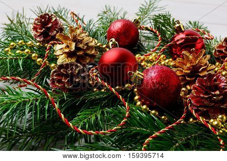 Christmas garland with red ornaments and golden pine cones. Christmas table centerpiece with golden decor.