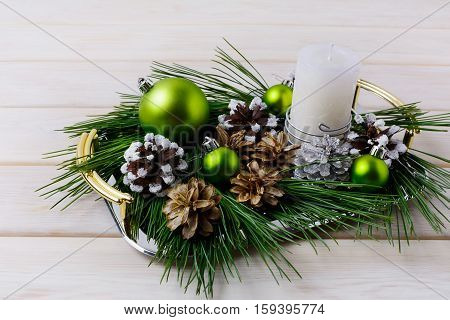 Christmas centerpiece with silver snowy and bleached pine cones. Christmas background with candle and ornaments on the serving tray. Copy space.