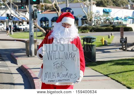 Santa Claus stands on the street with a  Will Work for Milk and Cookie cardboard sign. Homeless Santa with sign. Will Work for food.