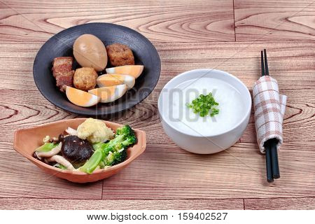 Rice gruel and stewed boiled egg with tofu and streaky pork and fried mixed vegetable served .