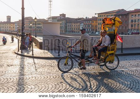 People On A Cycle Rickshaw Riding Over An Arno Bridge In Pisa, Italy
