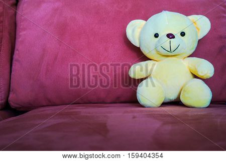 Yellow bear doll sitting on couch, Soft yellow bear doll sitting on sofa