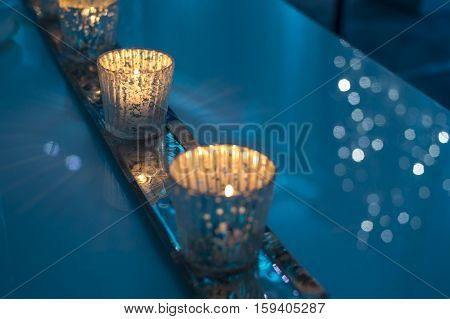 Christmas sparkling lights card with candles in a wintery romantic relaxing blue lit room. A perfect winter indoor scene for magical illuminated Christmas or New Years Holiday entertaining, announcement, invitation or card with copy space