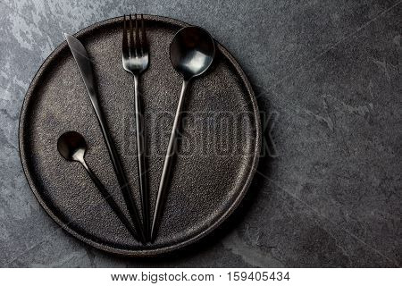 Black cutlery set - knife, spoon, fork, tea spoon on black plate on stone background. Top view