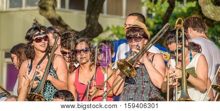 27 November, 2016. Band of women in sunglasses playing trombone in the street at sunny day at Festival Fanfare Activist Festival de Fanfarras Ativistas - HONK RiO 2016 at Leme, Rio de Janeiro, Brazil
