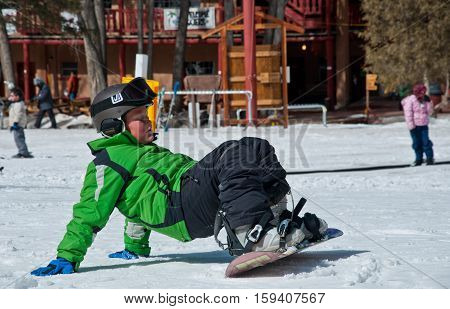Young Child Boy Trying to stand up while learning how to Snowboard. Winter Ski Resort Ski Lessons teaching a younger generation winter sports. Editorial: February 28th 2016 - Santa Fe , New Mexico , USA