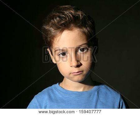 Cute little boy on black background