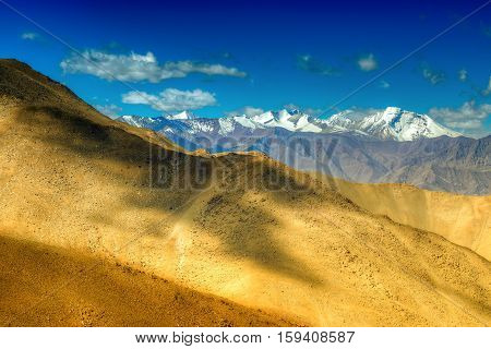 Rocky landscape of Ladakh with blue sky and ice peaks brown stones and rocks at Changla pass play of light and shodow on the mountain Leh Ladakh Jammu and Kashmir India