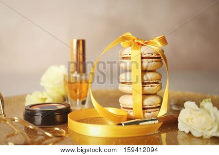Tied with ribbon macaroons and beauty accessories on golden surface
