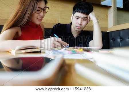 Education concept. Students studying and brainstorming campus concept. Close up of students discussing their subject on books textbooks and writing to notebook. Selective focus.